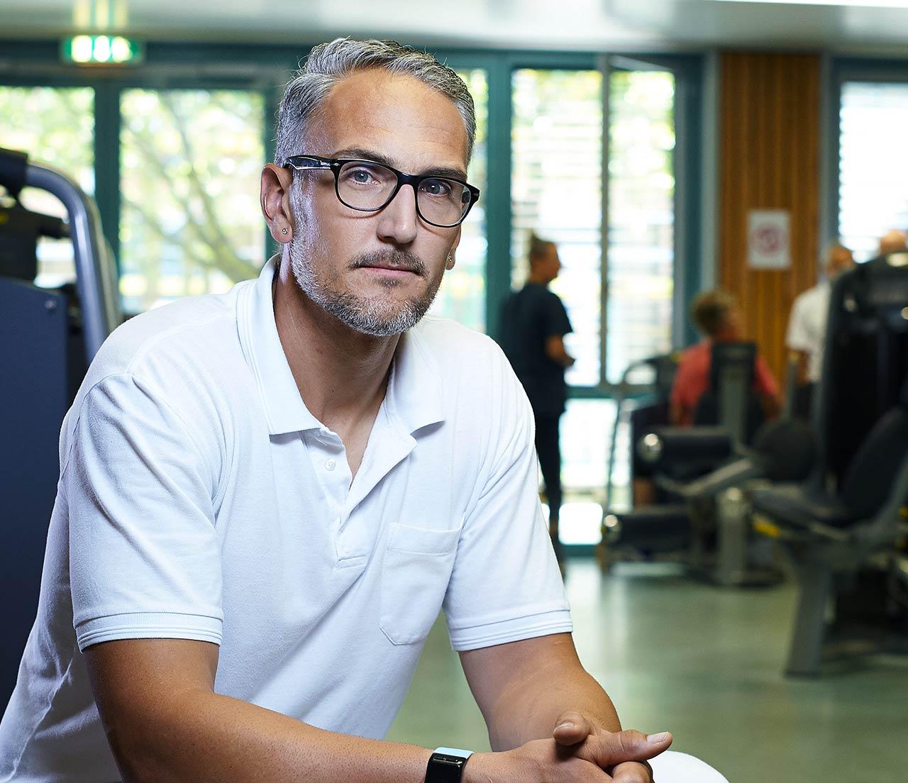 Aufnahme eines Mitarbeiters in einem Raum voller Sportgeräte während er über einen bewegenden Moment seines Jobs erzählt